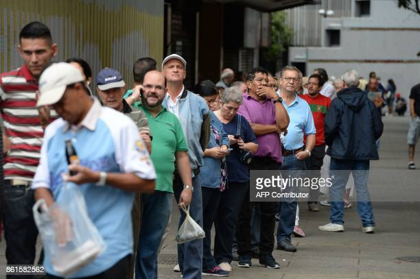 Venezuelans queue at a polling station before voting during regional elections in Caracas' municipality of Chacao where people chose the governor for...
