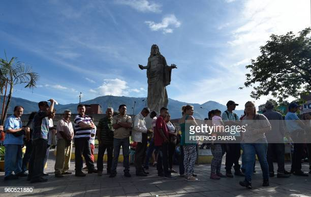 Venezuelans queue at government party checkpoints to present their Homeland Cards after casting their votes during the presidential elections in...