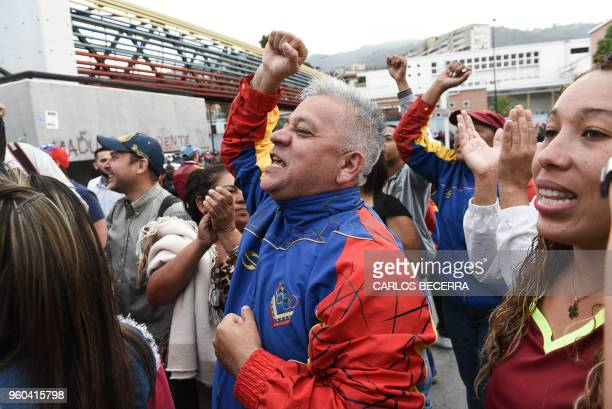 Venezuelans show thier support to incumbent president Nicolas Maduro outside a polling station as they wait to cast their vote during the...
