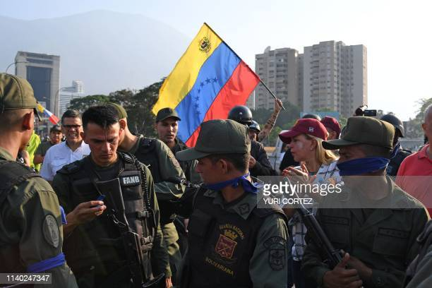 Venezuelans stand next to members of the security forces in Caracas on April 30 2019 Venezuelan opposition leader and selfproclaimed acting president...