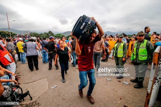 Venezuelans walk in front of Venezuelan National Guard officers as they cross the Simon Bolivar international bridge in Cucuta Colombia in the border...