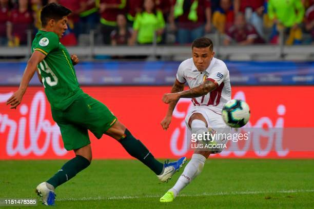 TOPSHOT Venezuela's Darwin Machis strikes the ball past Bolivia's Ramiro Vaca to score during their Copa America football tournament group match at...