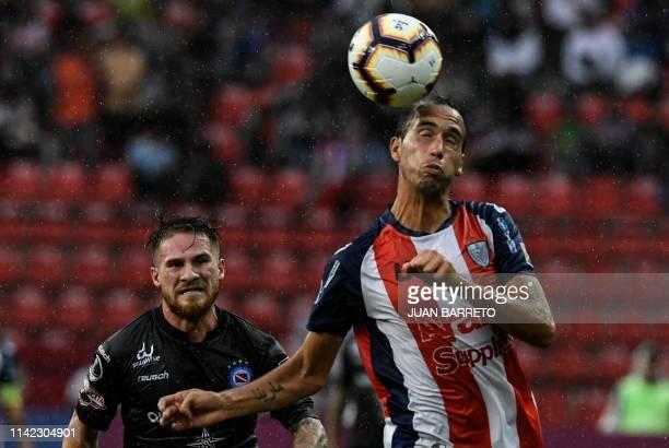 Venezuela's Estudiantes de Merida Oscar Sainz heads the ball next to Argentina's Argentinos Juniors Alexis Mac Allister during their Copa...