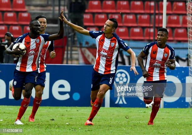 Venezuela's Estudiantes de Merida Wilson Mena celebrates with teammate Luz Rodriguez after scoring against Argentina's Argentinos Juniors during...