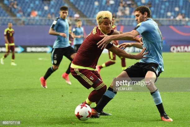 Venezuela's forward Adalberto Penaranda Maestre and Uruguay's defender Agustin Rogel compete for the ball during the U20 World Cup semifinal football...