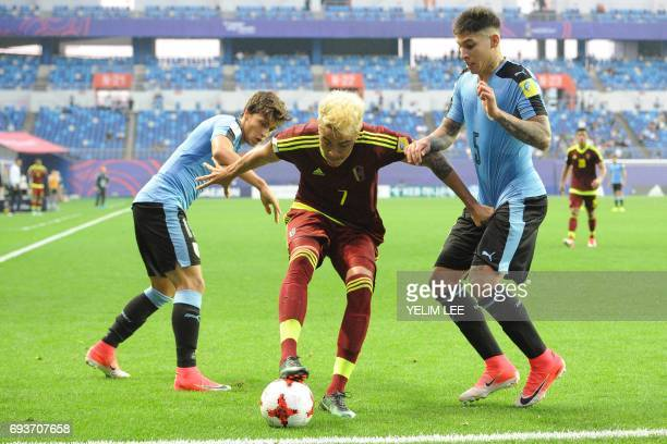 Venezuela's forward Adalberto Penaranda Maestre controls the ball next to Uruguay's forward Agustin Canobbio and defender Mathias Olivera during the...