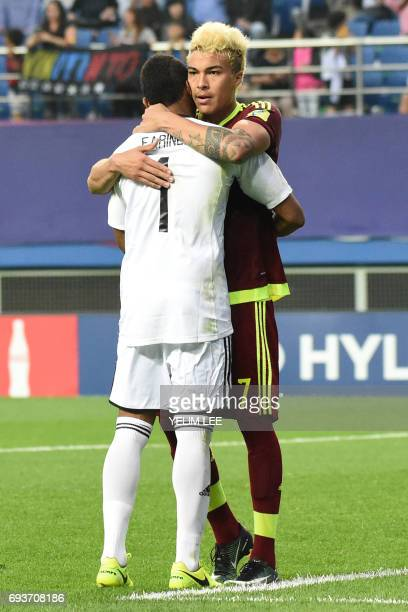 Venezuela's forward Adalberto Penaranda Maestre hugs Venezuela's goalkeeper Wuilker Farinez during the U20 World Cup semifinal football match between...