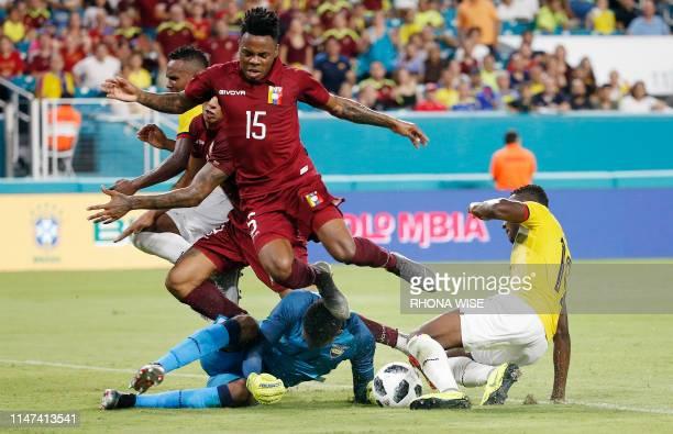 Venezuela's forward Jhon Murillo collides with Ecuador's goalkeeper Alexander Domínguez and Ecuador's forward Enner Valencia as he tries to score...