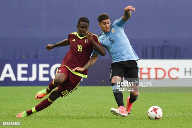Venezuela's forward Sergio Cordova and Uruguay's defender Mathias Olivera compete for the ball during the U20 World Cup semifinal football match...