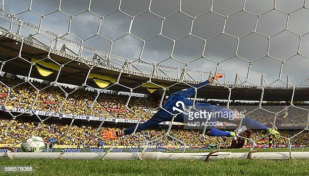 Venezuela's goalkeeper Daniel Hernandez jumps for the ball after Colombia's midfielder James Rodriguez shot in the Roberto Melendez stadium during...