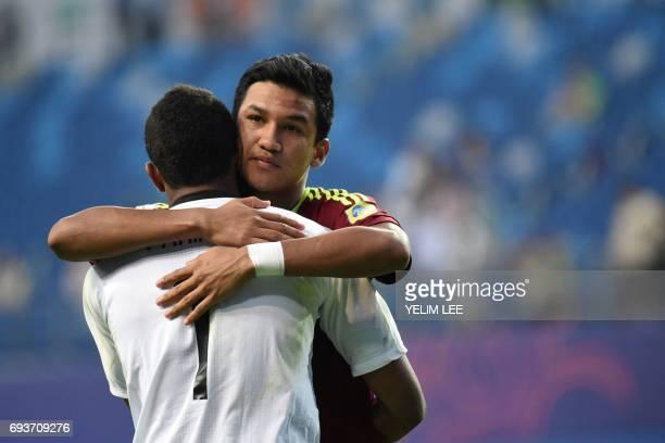 Venezuela's goalkeeper Wuilker Farinez hugs forward Samuel Sosaduring the penalty shootout in the U20 World Cup semifinal football match between...