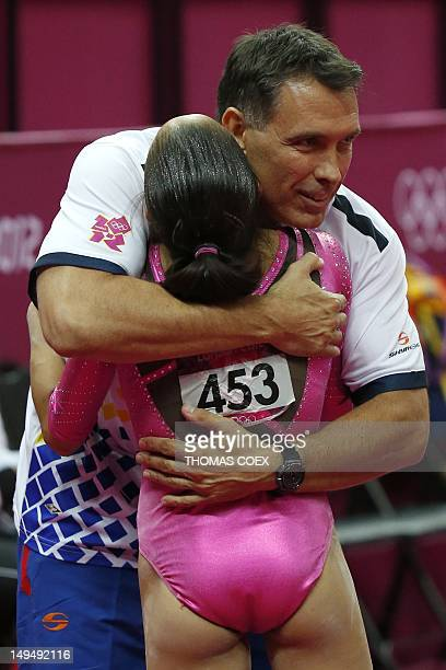 Venezuela's gymnast Jessica Lopez is congratulated by a member of her team after performing during the women's qualification of the artistic...