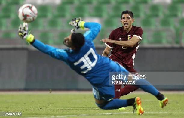Venezuela's Jefferson Savarino shoots on goal as Iran's goalkeeper Amir Abedzadeh stretches to catch the ball during the friendly football match...