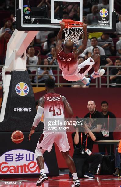 Venezuela's Miguel Ruiz hangs on the rim as Venezuela's Nestor Colmenares looks on after scoring during the Basketball World Cup Group A game between...