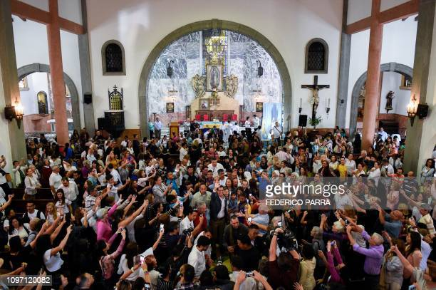 TOPSHOT Venezuela's National Assembly head and selfproclaimed acting president Juan Guaido waves as he leaves after attending a mass at the Nuestra...