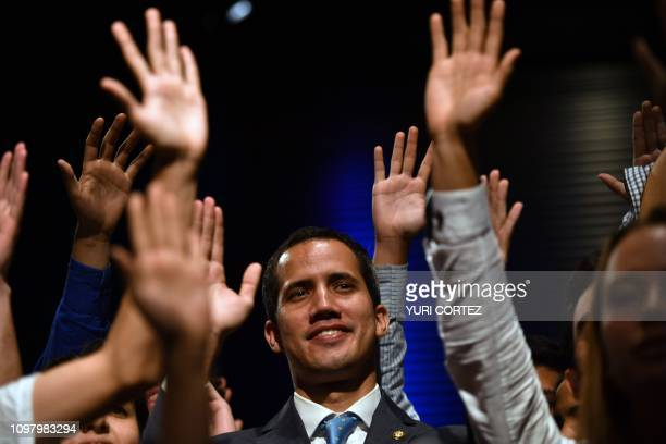 TOPSHOT Venezuela's National Assembly head and selfproclaimed acting president Juan Guaido raises his hands surrounded by students after speaking at...