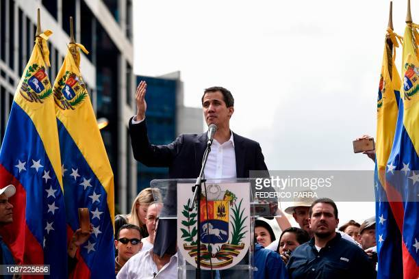 Venezuela's National Assembly head Juan Guaido waves to the crowd during a mass opposition rally against leader Nicolas Maduro in which he declared...