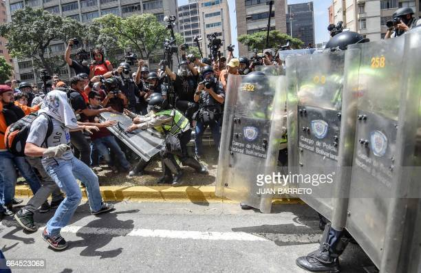 TOPSHOT Venezuela's opposition activists clash with riot police agents during a protest against Nicolas Maduro's government in Caracas on April 4...
