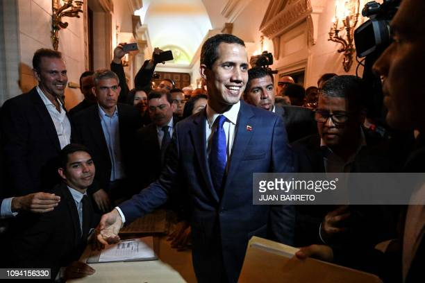 TOPSHOT Venezuela's opposition leader and selfproclaimed acting president Juan Guaido heads to a session of the National Assembly after signing the...
