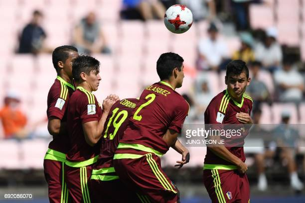 Venezuela's players react as a US player attempts a freekick during their U20 World Cup quarterfinal football match between Venezuela and the US in...