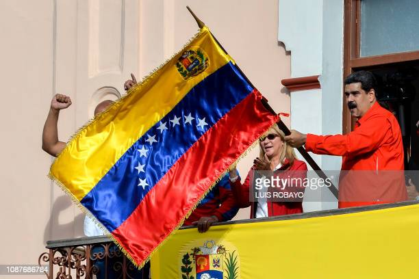 TOPSHOT Venezuela's President Nicolas Maduro flanked by his wife Cilia Flores holds a Venezuelan flag while speaking from a balcony at Miraflores...