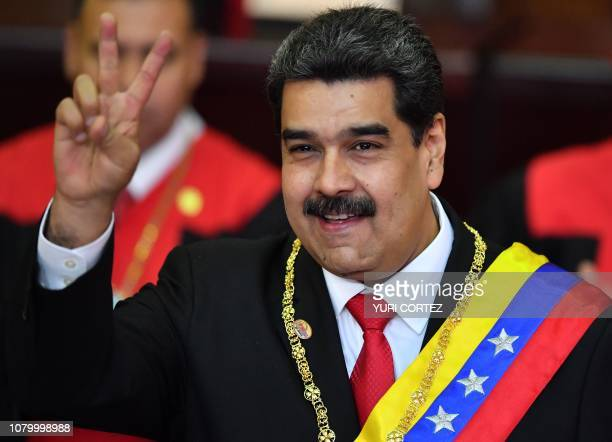 TOPSHOT Venezuela's President Nicolas Maduro flashes the victory sign after being swornin for his second mandate at the Supreme Court of Justice in...