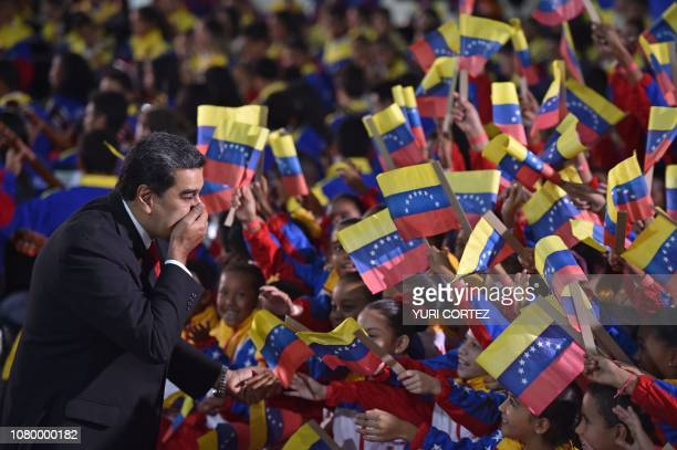 TOPSHOT Venezuela's President Nicolas Maduro greets children upon arrival for the inauguration ceremony of his second mandate at the Supreme Court of...