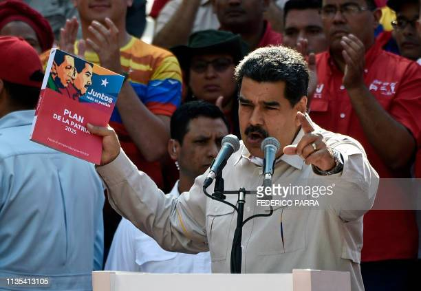 Venezuela's President Nicolas Maduro holds the government's plan for 2025 during a rally at the Miraflores Palace in Caracas Venezuela on April 6...