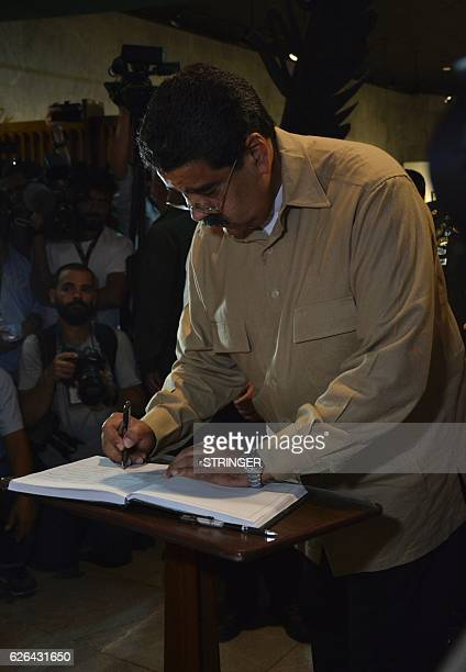 Venezuela's President Nicolas Maduro signs the condolences book after paying his last respects to Cuban revolutionary icon Fidel Castro in Havana on...