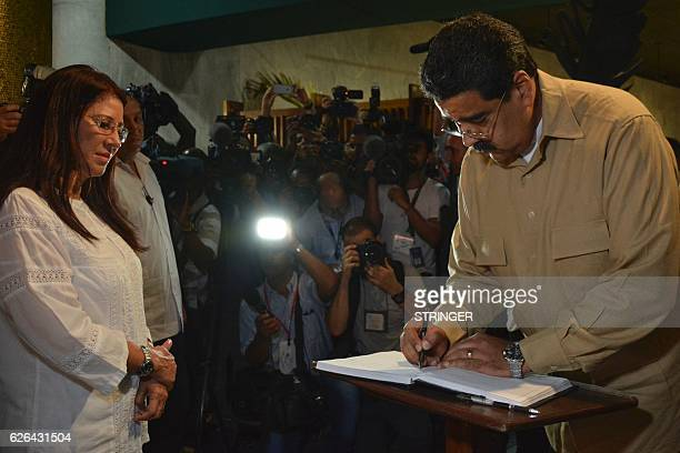Venezuela's President Nicolas Maduro signs the condolences book as his wife Cilia Flores looks on after paying their last respects to Cuban...