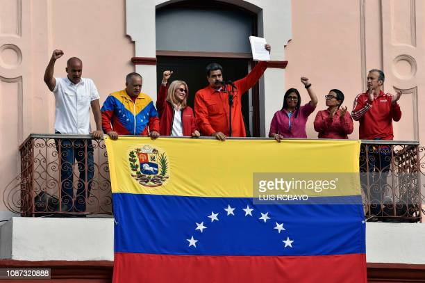 Venezuela's President Nicolas Maduro speaks to a crowd of supporters at the Miraflores Palace flanked by his wife Cilia Flores Venezuelan...