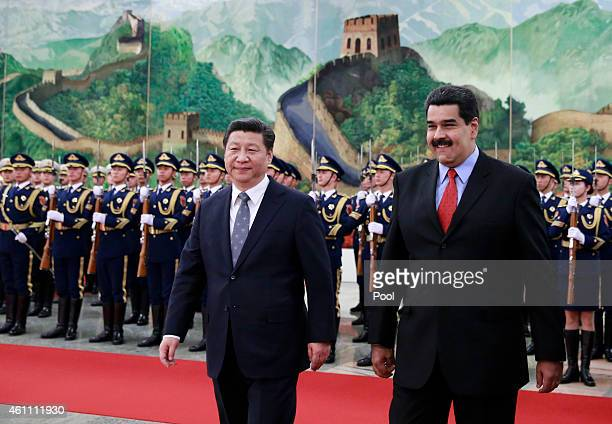 Venezuela's President Nicolas Maduro walks with Chinese President Xi Jinping as they arrive to a welcoming ceremony at the Great Hall of the People...