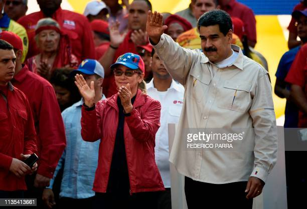 Venezuela's President Nicolas Maduro waves at supporters next to First Lady Cilia Flores during a rally at the Miraflores Palace in Caracas Venezuela...