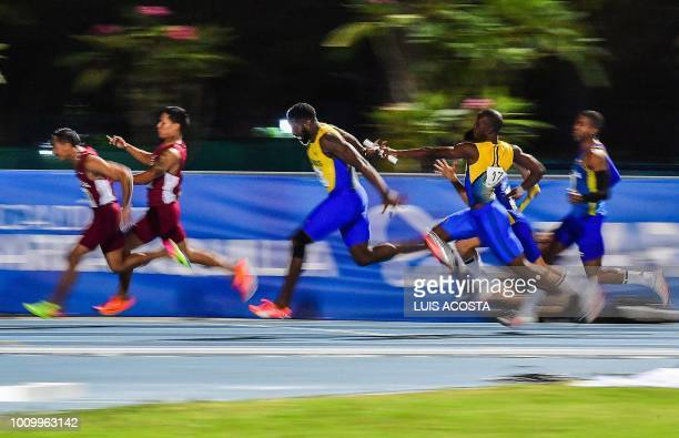 Venezuela's Rafael Vazquez and Arturo Rairez and Barbados' Ellis Burkheart and Mario Burke compete in the Men's 4x100m relay final during the 2018...