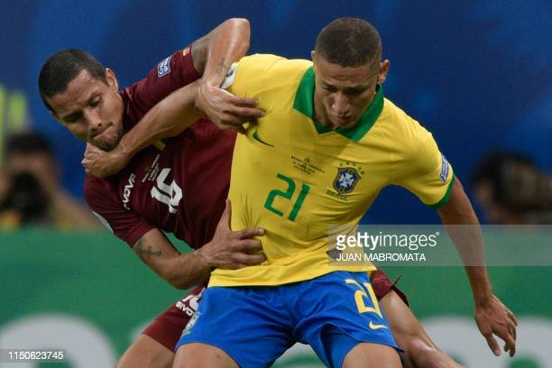TOPSHOT Venezuela's Roberto Rosales and Brazil's Richarlison vie for the ball during their Copa America football tournament group match at the Fonte...
