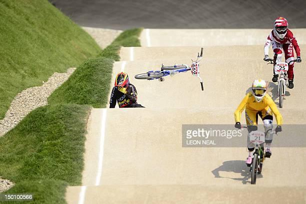 Venezuela's Stefany Hernandez comes off her bike as Australia's Lauren Reynolds and Latvia's Sandra Aleksejeva ride by during the BMX cycling women's...
