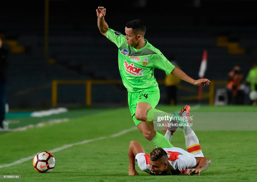Venezuela's Tachira player Damir Ceter Valencia (top) vies for the ball with Santa Fe player Juan Roa during their Libertadores 2018 football match against Santa Fe at El Campin stadium in Bogota on February 8, 2018. /
