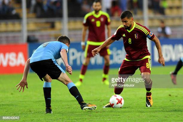 Venezuela's Tomas Rincon is marked by Uruguay's Federico Valverde during their 2018 World Cup qualifier football match in San Cristobal Venezuela on...