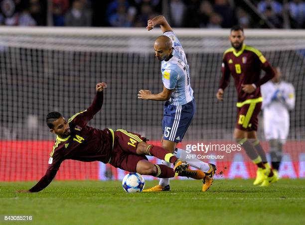 Venezuela's Yangel Herrera vies for the ball with Argentina's Guido Pizarro during their 2018 World Cup qualifier football match in Buenos Aires on...