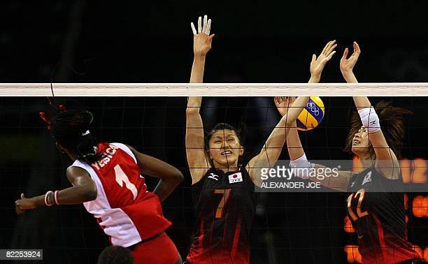 Venezuela's yessica Paz slams the ball past Japan's Sachiko Sugiyama and Saori Kimura during a women's volleyball preliminary match of the Beijing...