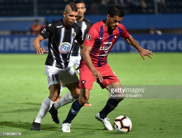 Venezuela's Zamora player Antonio Romero vies for the ball with Paraguay's Cerro Porteno player Salustiano Candia during a Copa Libertadores football...