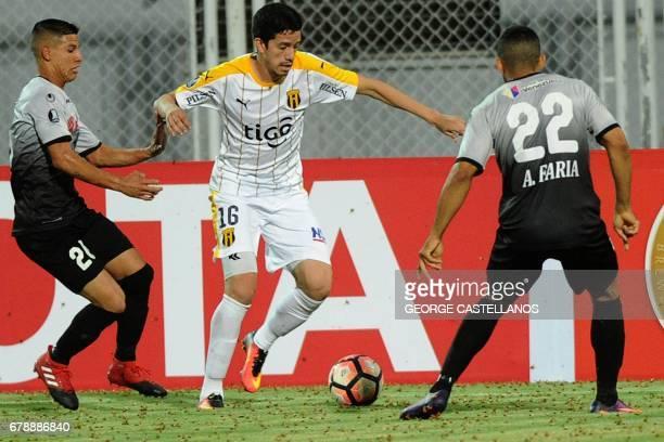 Venezuela's Zamora players Diego Garcia and Angel Farias vie for the ball with Alberto Contrera of Paraguay' Guarani during their Copa Libertadores...