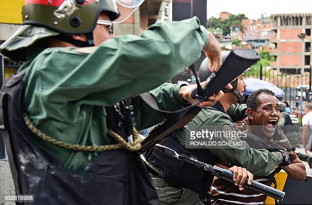 TOPSHOT Venezuelean National Guard clashes with citizens protesting against the severe food and medicine shortages in Caracas Venezuela on June 8...