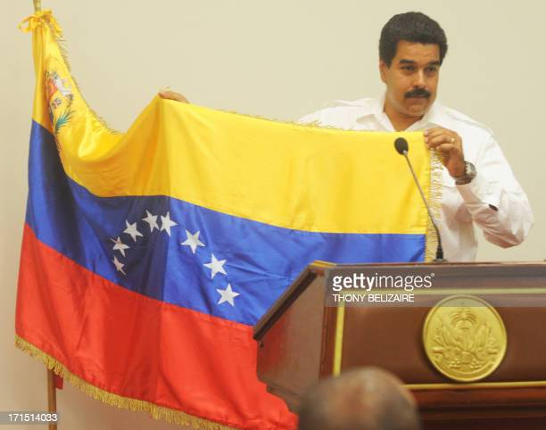 Venezuelian President Nicolas Maduro shows his national flag while speaking on June 25 2013 at the presidential palace in PortauPrince Haiti...