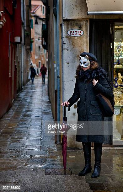 Venice Carnival 2008 Masked reveller waiting on wet Venice back street