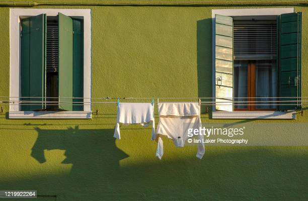venice, italy. 5 march 2005. detail of colourful house with windows and clothes drying on line on the venetian island of burano. - drying stock pictures, royalty-free photos & images