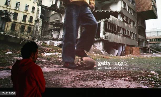 "Visitor looks at the video ""Bouncing Skull"" by Italian artist Paolo Canevari, showing a boy dribbling with a skull in Sarajevo, at the 52nd..."