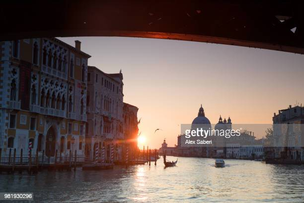 A gondola makes its way to the Santa Maria della Salute at sunrise on the Grand Canal.