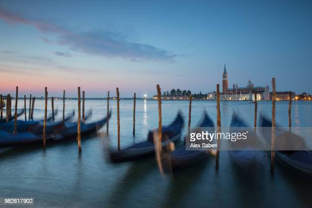 Long exposure of blue gondolas at dawn with the church of San Giorgio Maggiore in the background.