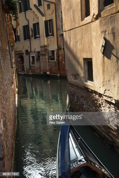 A Gondola makes its way up a Venetian canal at sunrise.